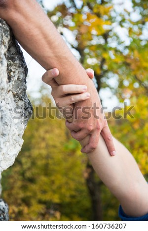Hands of climber on brink of rock needing the help. - stock photo
