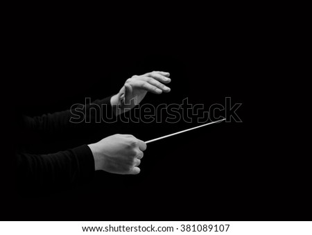 Hands of conductor on a black background in black and white - stock photo