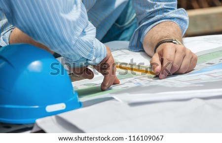 Hands of construction professionals discussing details of project over drawings - stock photo