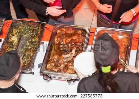 Hands of cook serving food at a catered event - stock photo