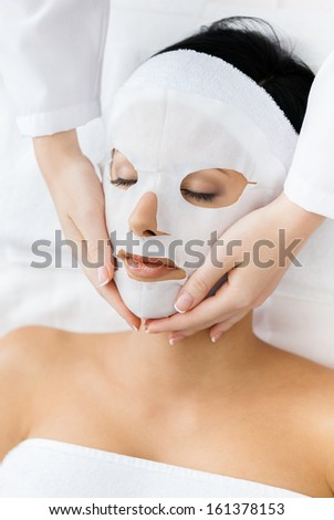 Hands of cosmetologist apply mask to face of woman. Concept of beauty and youth - stock photo