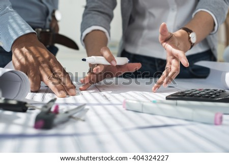 Hands of creative team discussing plan of the building - stock photo