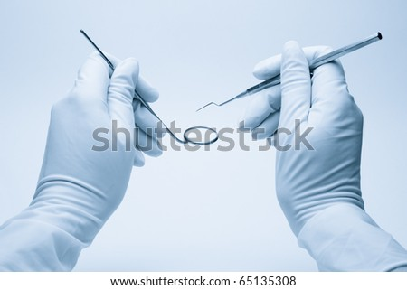hands of dentist holding his tools during patient examination - stock photo