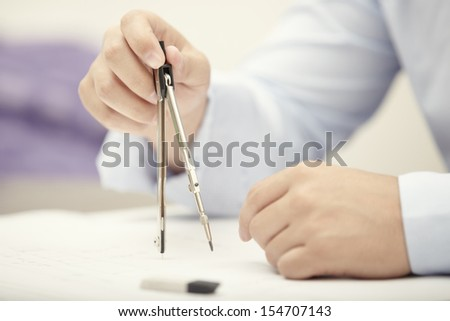 Hands of engineer working with compasses - stock photo