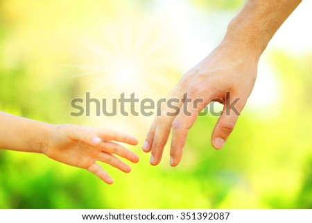 Hands of father and son holding each other - stock photo