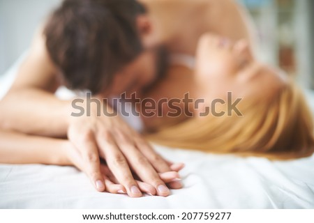 Hands of female and male lying on bed - stock photo