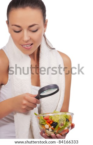 hands of girl exploring vegetable salad using magnifying glass - stock photo