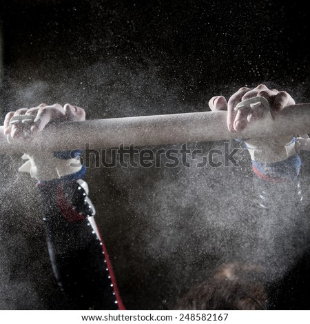 hands of gymnast with chalk on uneven bars  - stock photo