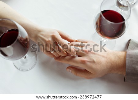 Hands of just married couple  tenderly holding each other, wearing wedding rings - stock photo