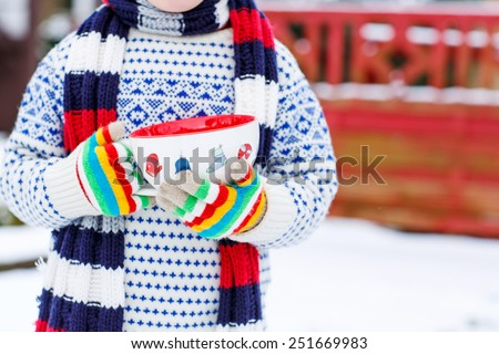 Hands of little child holding big cup with snowflakes and hot chocolate drink and marshmallows, outdoors with snow background. Kid boy in winter sweater, hat, long warm scarf and colorfull gloves.  - stock photo