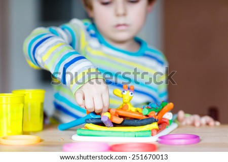Hands of little child playing with dough, colorful modeling compound, sitting at table at home or kindergarten, nursery. Creative leisure with kids. - stock photo