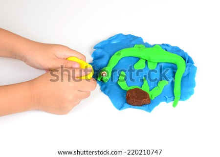 Hands of little girl making dinosaurs from colorful clay dough - stock photo