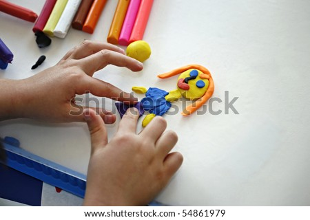 Hands of little girl making doll from colorful clay dough  (plasticine) 2 - stock photo