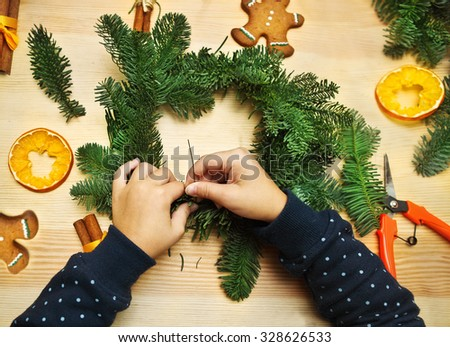 Hands of little girl spinning and decorating Christmas wreath - stock photo