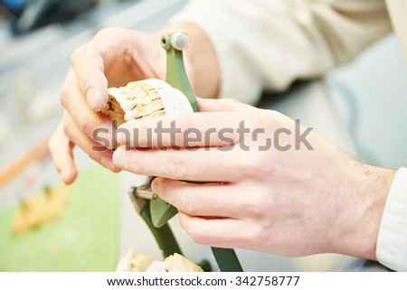 hands of male dental technician working with tooth dentures at prosthesis laboratory - stock photo