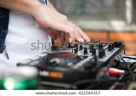 Hands of male Dj playing music on modern midi controller turntable. Digital device for mixing music on events and in studio.  - stock photo