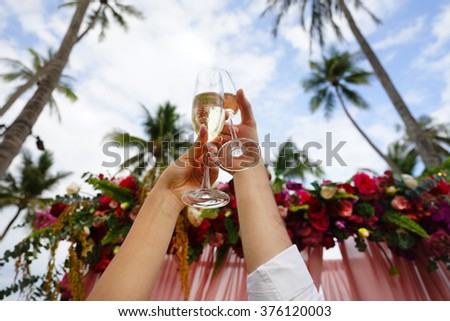 Hands of man and woman with glasses raised up against the wedding arch - stock photo