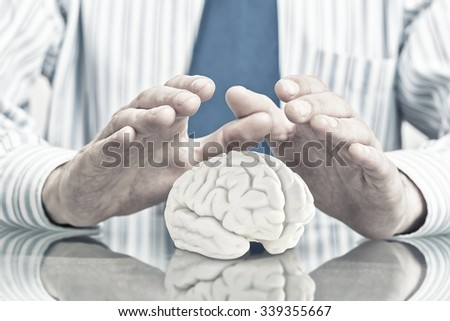 Hands of man holding with care human brain  - stock photo