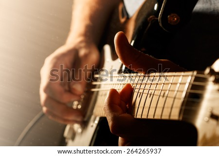 Hands of man playing electric guitar. Bend technique. Low key photo. - stock photo
