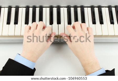 hands of man playing piano - stock photo