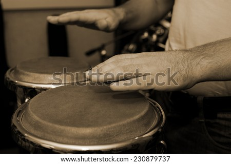 Hands of man playing the bongos - stock photo