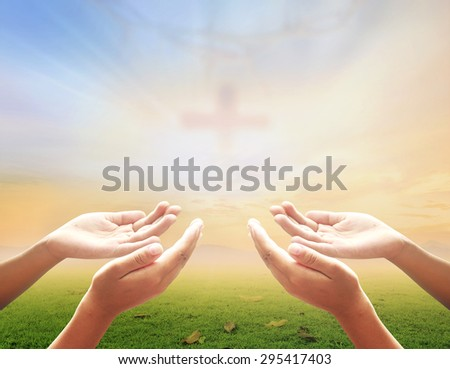 Hands of man praying over blurred crown of thorns and the cross on a sunset background. - stock photo