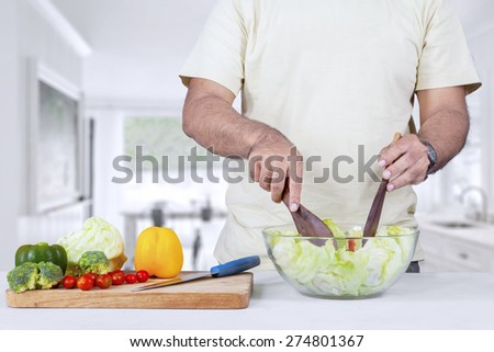 Hands of man preparing organic salad in the kitchen - stock photo