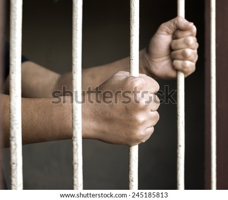 Hands of man prisoner gripping in and out on rusty prison bars - stock photo