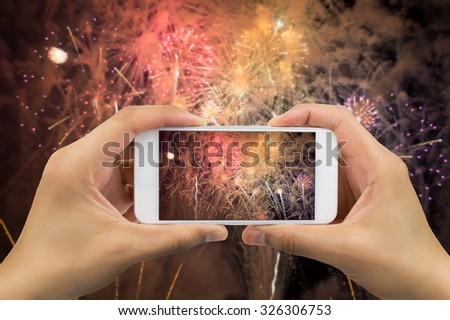 hands of man taking the photo to fireworks with the new smartphone - stock photo