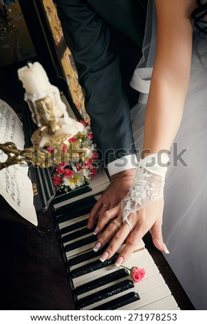 Hands of married man and woman with wedding rings laying on keys of piano with beige roses nearly - stock photo