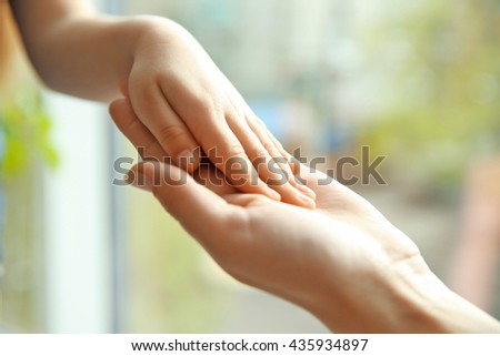 Hands of mother and child on natural background - stock photo