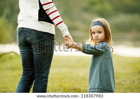 Hands of mother and daughter holding each other. - stock photo