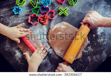 Hands of mother and daughter using rolling pins together in the kitchen. Mother teaching daughter how to bake cookies for holidays. Easter baking preparation. Easter food concept. Top view. - stock photo