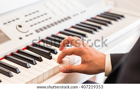 Hands of musician close-up. Pianist playing on electric piano - stock photo