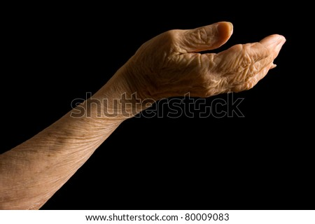 Hands of old woman on black background - stock photo
