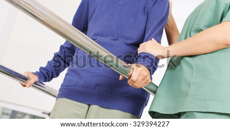 Hands of old woman on handles of a treadmill in physiotherapy - stock photo
