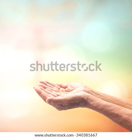 Hands of old woman praying over blurred bokeh Jesus on the cross at sunset background. Christmas, Worship, Forgiveness, Mercy, Humble, Repentance, Reconcile, Adoration, Glorify, Surrender concept. - stock photo