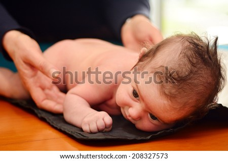 Hands of Pediatrician nurse checks infant baby body development examination. - stock photo