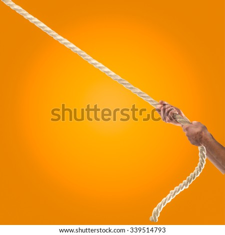 Hands of people pulling the rope on orange background.  Competition concept - stock photo
