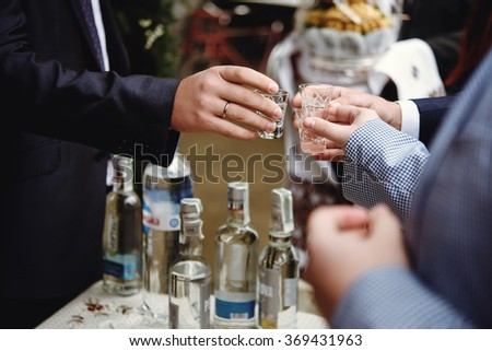 hands of people with  glasses of alcohol, celebrating and toasting, wedding or birthday event - stock photo