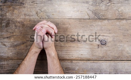 Hands of praying young man on a wooden desk background. - stock photo