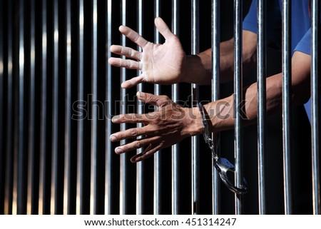 hands of prisoner in jail - stock photo