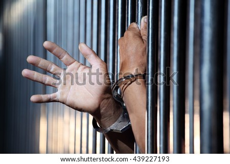 hands of prisoner in jail as background. - stock photo