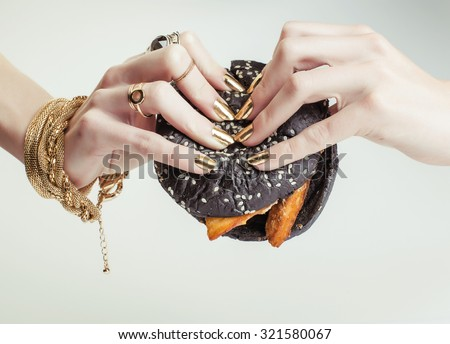 hands of rich woman with golden manicure and jewelry holding black hamburger close up - stock photo