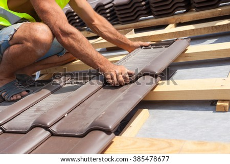 Hands of roofer laying tile on the roof. Installing natural red tile. - stock photo