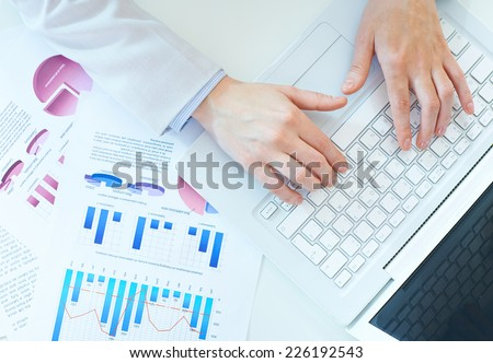 Hands of secretary pushing laptop buttons - stock photo