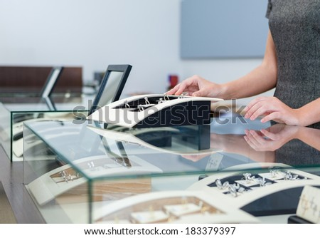 Hands of shop assistant at the window case with rings at jeweler's shop. Concept of wealth and luxurious life - stock photo