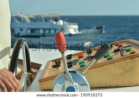 Hands of skipper on a motor boat - stock photo