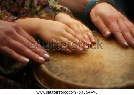 Hands  of teacher and student on drum - stock photo