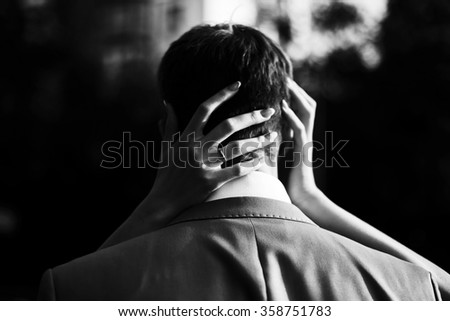 hands of the bride hugging the groom by the neck  - stock photo